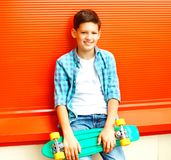 Fashion smiling teenager boy with skateboard in a checkered shirt. On orange background royalty free stock images