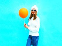 Fashion smiling woman with an air balloon on blue background Royalty Free Stock Image