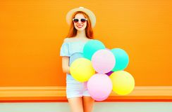 Fashion smiling woman with an air colorful balloons on orange Royalty Free Stock Images