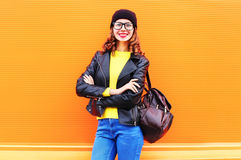 Fashion smiling woman with bag wearing black hat, rock jacket over colorful orange background Royalty Free Stock Photo