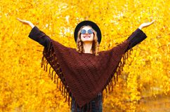 Fashion smiling woman enjoys an autumn park in black round hat. Knitted poncho stock images