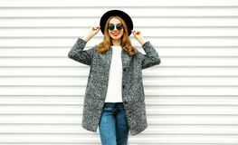 Fashion smiling woman in gray coat, black round hat posing. On white wall background on street city stock photos