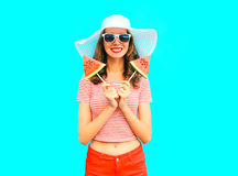 Fashion smiling woman is holding a two slices watermelon in the form of ice cream. A colorful blue background Stock Image