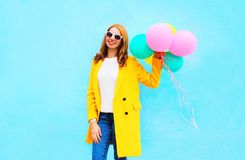 Fashion smiling woman holds an air balloons wearing a yellow coat Stock Image