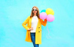 Fashion smiling woman holds an air balloons in yellow coat Royalty Free Stock Photography