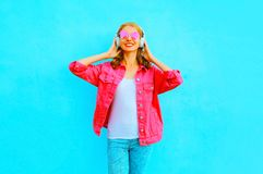 Fashion smiling woman listens to music in wireless headphones in pink denim jacket Royalty Free Stock Photo