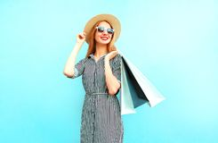 Fashion smiling woman with shopping bags in striped dress. Round straw hat on blue background stock photo
