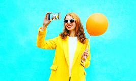 Fashion smiling woman takes a picture self portrait on smartphone Stock Image