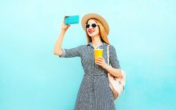 Fashion smiling woman takes a picture self portrait on smartphone. Holds cup of juice with backpack on blue background stock image