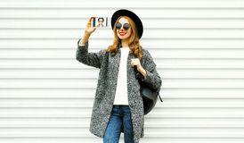 Fashion smiling woman taking selfie by smartphone in gray coat. Black round hat on white wall background on street city stock images