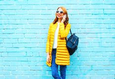 Fashion smiling woman talks on a smartphone on brick background. Fashion smiling woman talks on a smartphone on a brick background Stock Image