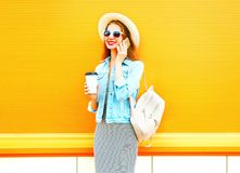 Fashion smiling woman talks on a smartphone with coffee cup. On a orange background Royalty Free Stock Images