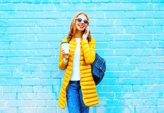 Fashion smiling woman talks on a smartphone holds coffee cup. On a blue background Stock Photo