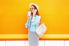 Fashion smiling woman talks on a smartphone holds coffee cup. On a orange background Stock Photo