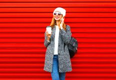 Fashion smiling woman talks on a smartphone holds coffee cup on a red. Background Royalty Free Stock Photos
