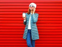 Fashion smiling woman talks on a smartphone holds coffee cup. On a red background in the city Stock Image