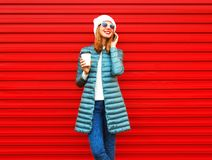 Fashion smiling woman talks on a smartphone holds coffee cup on red. Background Stock Image