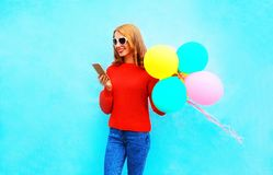 Fashion smiling woman is using smartphone with an air balloons o Royalty Free Stock Photo
