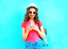 Fashion smiling woman using smartphone wearing straw hat and backpack over colorful blue. Background Stock Images