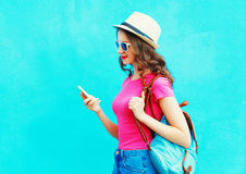 Fashion smiling woman using smartphone wearing straw hat and backpack over colorful blue background. Profile view Stock Photography
