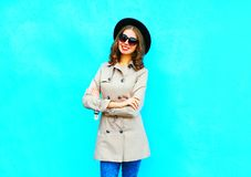Fashion smiling woman wearing a coat and black round hat. On a blue background stock images