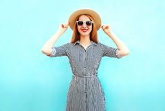 Fashion smiling woman wearing a striped dress, summer straw hat. On blue background stock photography