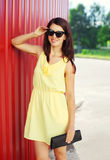 Fashion smiling woman wearing yellow dress and sunglasses with handbag clutch Stock Photos