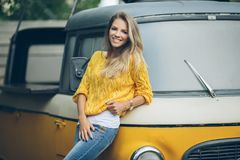 Fashion smiling woman is wearing yellow sweater near old retro bus Stock Images