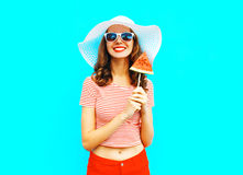 Fashion smiling young woman is holding a slice of watermelon in the form of ice cream. A colorful blue background Royalty Free Stock Photography