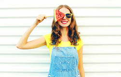 Fashion smiling young woman holding a slice of watermelon in the form of ice cream. Over a white background stock photo