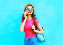 Fashion smiling young woman talking on a smartphone over a colorful blue background. Fashion smiling young woman talking on a smartphone over colorful blue Royalty Free Stock Photo
