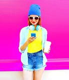 Fashion smiling young woman using smartphone holds a coffee cup Stock Image