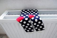 Fashion socks drying on heating radiator Stock Image