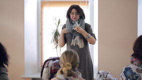 Fashion specialist teaches how to tie an oblong thick winter scarf. stock video footage