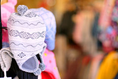 Fashion 3. A stand with woollen hats with brightly coloured and defocussed garments in the background Stock Photo