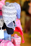 Fashion 4. A stand with woollen hats with brightly coloured and defocussed garments in the background Stock Photo