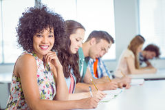 Fashion student smiling at camera in class Stock Photography