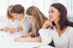 Fashion students taking notes in class. At the college Stock Photos