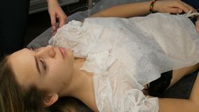 Fashion studio, the model is preparing for the show. Teen girl lies on a special couch, designer prepares her image. Fashion studio, the model is preparing for stock video footage