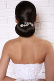 Fashion studio photo of elegant bride with luxurious hairstyle. In elegant wedding dress,back view stock photo