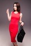 Fashion studio photo of elegant nude woman with bag. Photo of elegant woman  in red dress with bag Stock Photos