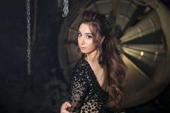 Fashion studio photo of gorgeous sensual latina woman with dark hair in luxurious dress with rhinestones looking to. Camera. Dark industrial studio interior royalty free stock photos