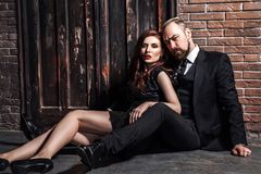 Fashion studio photo of sexy  couple of ginger woman and blonde man dressed wearing classic style, sitting on the flor