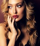 Beautiful girl with blond curly hair and evening makeup. Fashion studio portrait of beautiful girl with blond curly hair and evening makeup stock photography