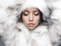 Beautiful woman in white fur coat and fur hat Stock Photo
