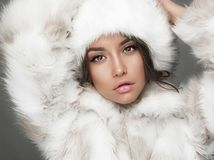 Beautiful woman in white fur coat and fur hat. Fashion studio portrait of beautiful lady in white fur coat and fur hat. Winter beauty in luxury. Fashion fur Royalty Free Stock Image