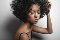 Beautiful woman with afro curls hairstyle. Fashion studio portrait of beautiful woman in black dress with afro curls hairstyle. Fashion and beauty Royalty Free Stock Photos
