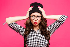 Fashion studio portrait of pretty young hipster brunette woman with glasses , wearing stylish urban t shirt and hat, over pink bac Stock Photos