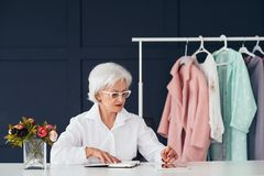 Fashion style assistance woman senior business. Fashion style assistance. Senior business lifestyle. Confident elderly woman at workplace browsing tablet royalty free stock image