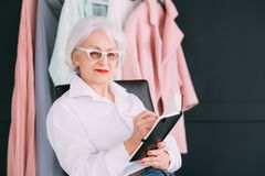 Fashion style assistance woman senior lifestyle. Fashion style assistance. Senior lifestyle. Confident elderly woman looking at camera while making notes in day stock photos
